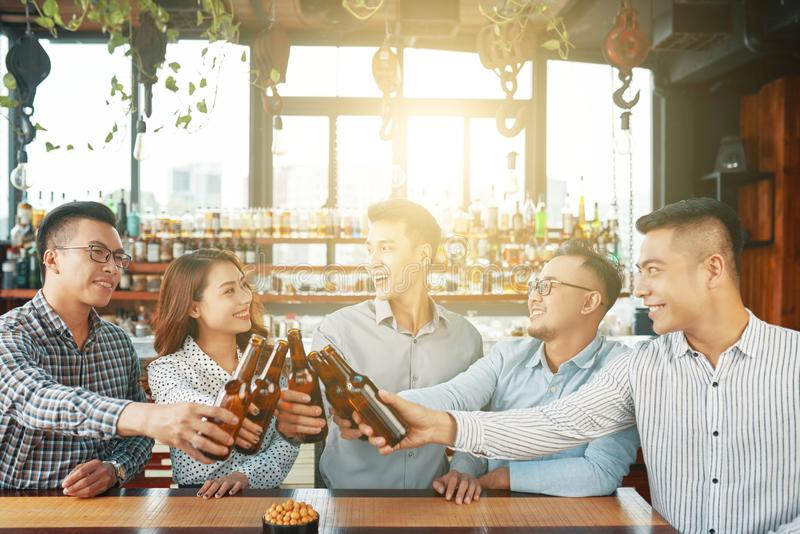 group-happy-asian-men-women-gathering-together-modern-sunny-bar-toasting-beer-bottles-cheerful-ethnic-people-123903101